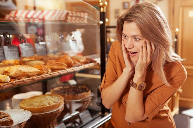 Reife frau, die im bäckereigeschäft einkauft