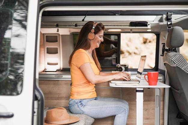 Reife frau, die in einem minivan-wohnmobil mit computer-laptop mit drahtlosem kopfhörer arbeitet