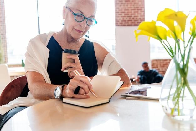 Reife frau, die in ihrem büro ein tagebuch schreibt