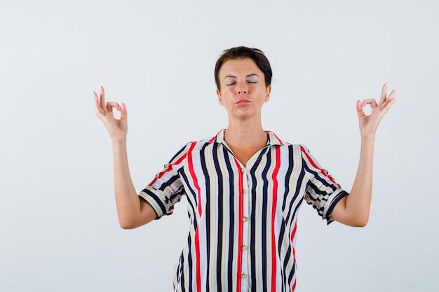 Reife frau, die in meditierender haltung in gestreifter bluse steht und entspannt schaut. vorderansicht.