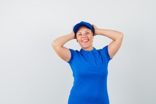 Reife frau, die kopf in händen im blauen t-shirt umklammert und froh aussieht.