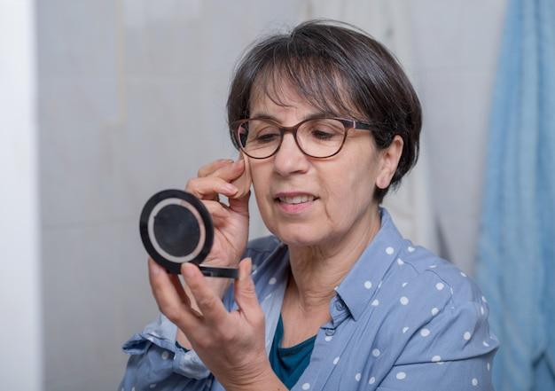 Reife frau, die make-up beim betrachten des kleinen spiegels tut