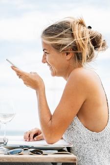 Reife frau, die mit ihrem handy spricht, das auf einem restaurant sitzt