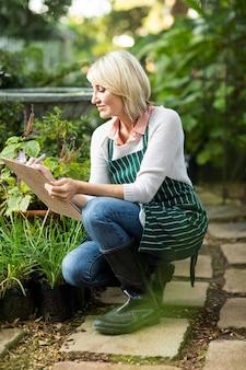Reife frau, die pflanzen untersucht