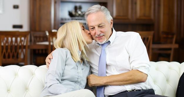 Reife frau, die seinen ehemann auf einem sofa küsst