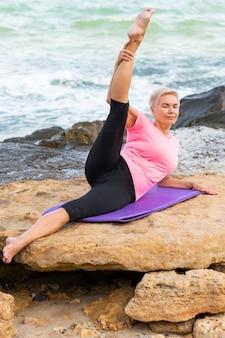 Reife frau, die sich am strand ausdehnt. auf einer yogamatte liegen.