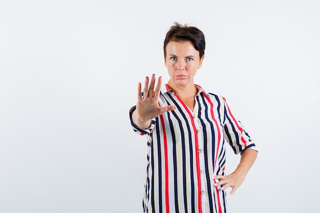 Reife frau, die stoppgeste zeigt, hand auf taille in gestreifter bluse hält und ernsthafte vorderansicht sieht.