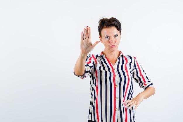 Reife frau, die stoppschild zeigt, hand auf taille in gestreifter bluse hält und ernst schaut, vorderansicht.