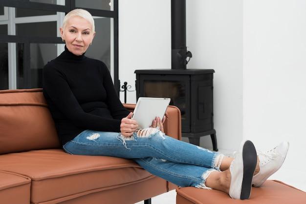 Reife frau, die tablette hält und auf dem sofa sich entspannt