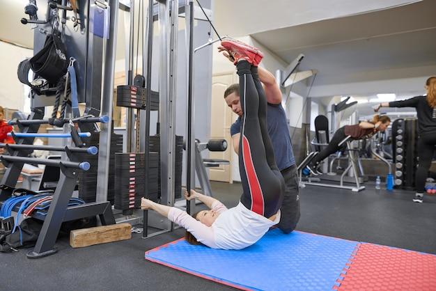 Reife frau, die übung auf dekompressionssimulatoren mit trainerrehabilitation tut