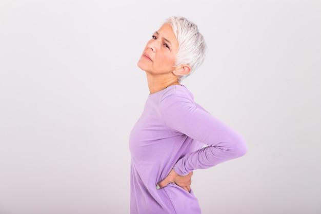 Reife frau, die unter rückenschmerzen leidet. reife frau, die mit rückenschmerzen ruht. weibliche schmerzen im unteren rücken. verletzung einer älteren frau, die unter rückenschmerzen leidet