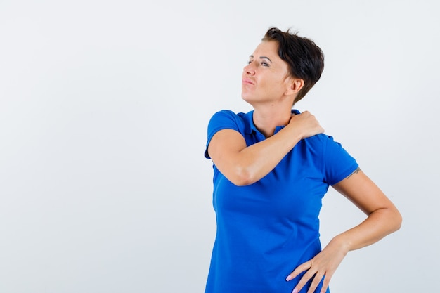 Reife frau, die unter schulterschmerzen im blauen t-shirt leidet und müde aussieht. vorderansicht.
