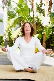 Reife frau, die yoga macht