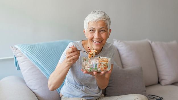 Reife frau, die zu hause auf einer weißen couch beim essen eines kleinen grünen salats, hauptinnenraum sitzt und sich entspannt.