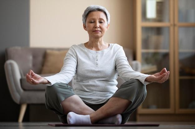 Reife frau, die zu hause meditiert