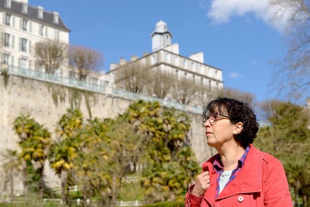 Reife frau geht in den park der französischen stadt