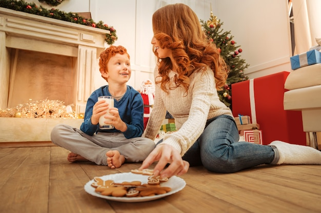 Reife frau greift nach einem lebkuchenmann, während sie neben ihrem sohn auf dem boden sitzt und ein angenehmes gespräch mit dem kind führt.