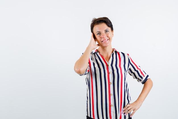 Reife frau hält eine hand am ohr, eine andere hand an der taille im gestreiften hemd und schaut glücklich, vorderansicht.
