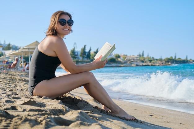 Reife frau im badeanzug-lesebuch der sonnenbrille, das auf sand durch meer sitzt