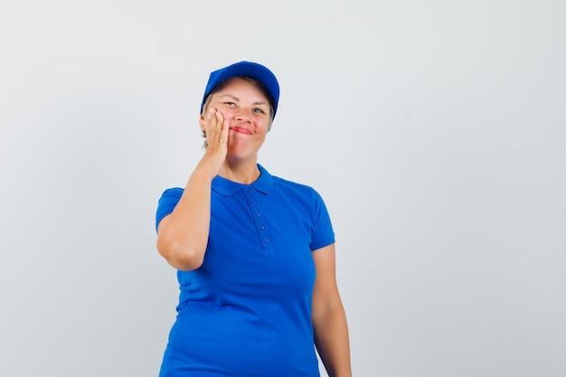 Reife frau im blauen t-shirt zieht ihre gesichtshaut auf wange.
