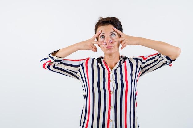 Reife frau im gestreiften hemd, das v zeichen nahe augen zeigt und ernsthafte vorderansicht schaut.