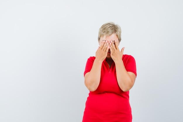 Reife frau im roten t-shirt, das hände auf augen hält und aufgeregt schaut.