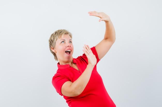 Reife frau im roten t-shirt, das hände hebt, um sich zu verteidigen und ängstlich aussieht