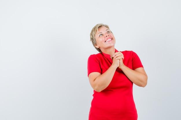 Reife frau im roten t-shirt, das hände in der gebetsgeste fasst und hoffnungsvoll aussieht.