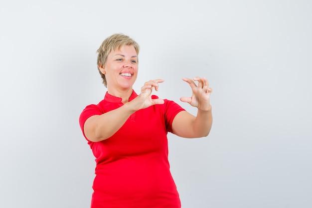 Reife frau im roten t-shirt, das vorgibt, foto auf handy zu machen und lustig zu schauen.