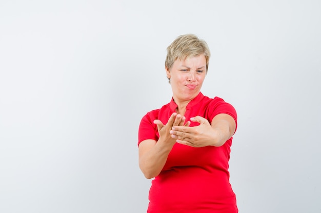 Reife frau im roten t-shirt, das vorgibt, handy zu halten.