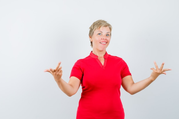 Reife frau im roten t-shirt, die hände in fragender geste streckt und zögernd aussieht