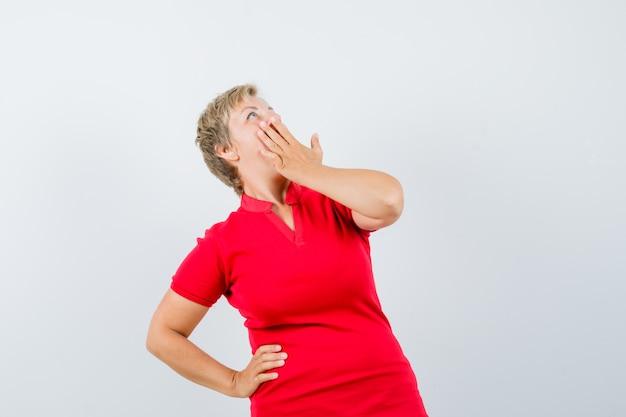 Reife frau im roten t-shirt, die hand auf mund hält und überrascht schaut.