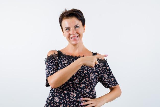 Reife frau in blumenbluse, schwarzer rock zeigt mit zeigefinger nach rechts, hält hand auf taille und sieht fröhlich aus, vorderansicht.