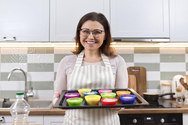 Reife frau in der schürze mit backblech mit cupcakes, die vorbereitet werden. frau zu hause kochen, hausgemachtes backen, gesundes essen, hobby
