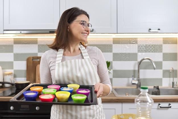 Reife frau in der schürze mit backblech mit cupcakes, die vorbereitet werden.