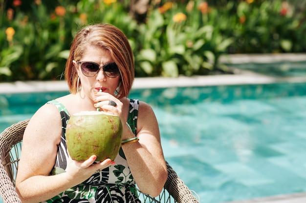 Reife frau in der sonnenbrille, die köstlichen kokosnusscocktail genießt, wenn sie durch schwimmbad ruht