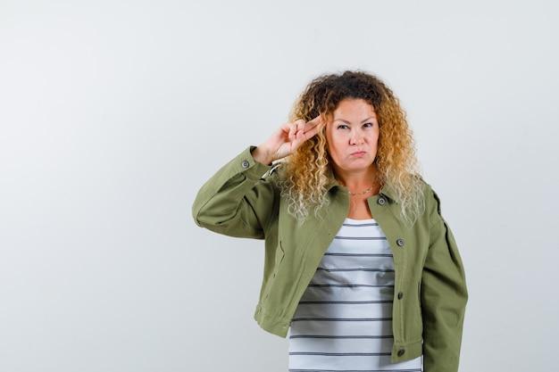 Reife frau in grüner jacke, t-shirt, das finger auf schläfe hält und selbstbewusst, vorderansicht schaut.