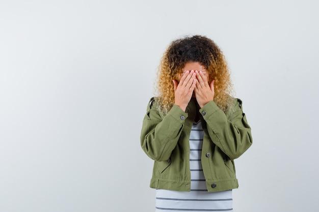 Reife frau in grüner jacke, t-shirt, das gesicht mit händen bedeckt und düster aussieht, vorderansicht.