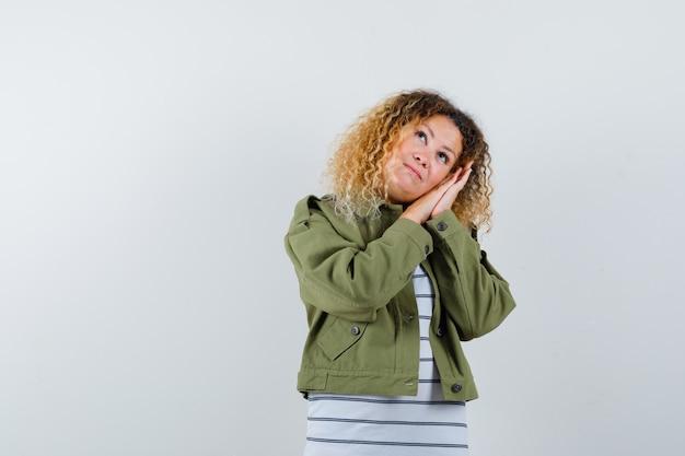 Reife frau in grüner jacke, t-shirt, das wangen auf hände lehnt, nach oben schaut und schläfrig schaut, vorderansicht.