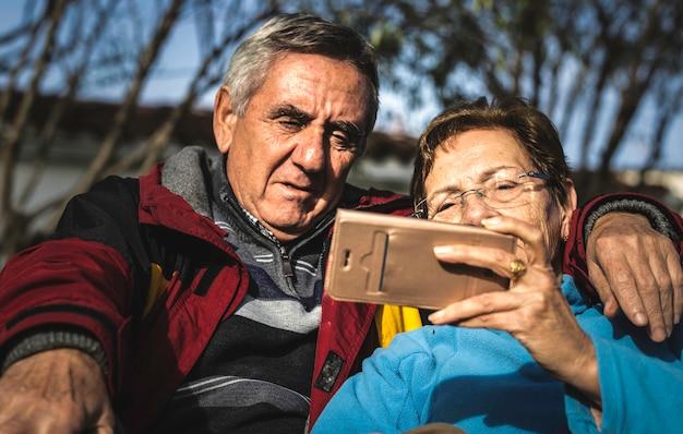 Reife frau mit dem smartphone umfasst von ihrem ehemann während beide, die im park sitzen