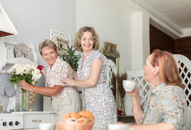 Reife frau mit der tochter, die blumenvase auf küchenarbeitsplatte während ihre mutter trinkt kaffee vereinbart