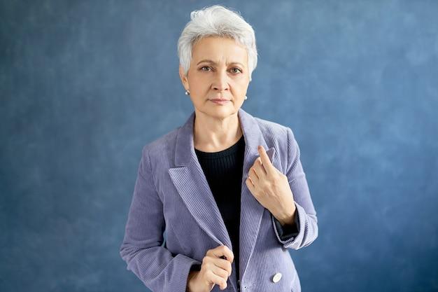 Reife frau mit grauem haar posiert mit violetter jacke