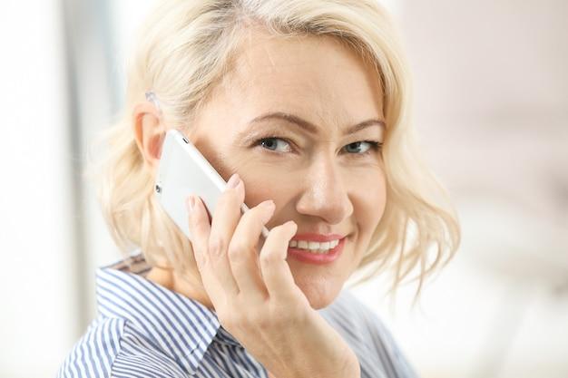 Reife frau mit hörgerät, das drinnen auf handy spricht