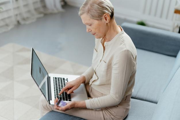 Reife frau mit kreditkarte, die ihren laptop für online-shopping nutzt