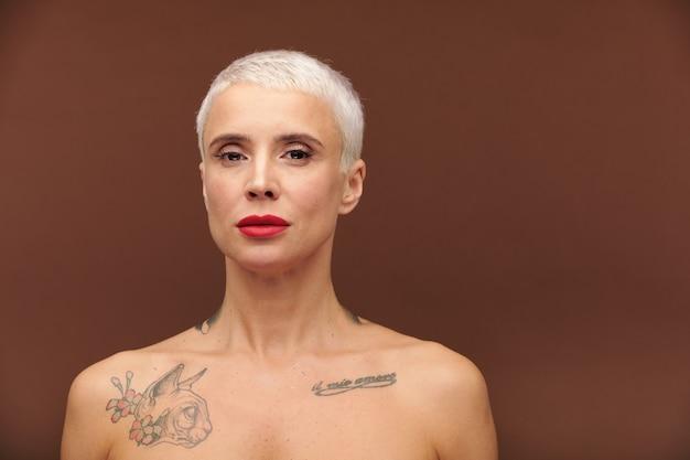 Reife frau mit kurzen blonden haaren, tätowierungen an hals und brust und rotem lippenstift auf den lippen, die dich anschaut