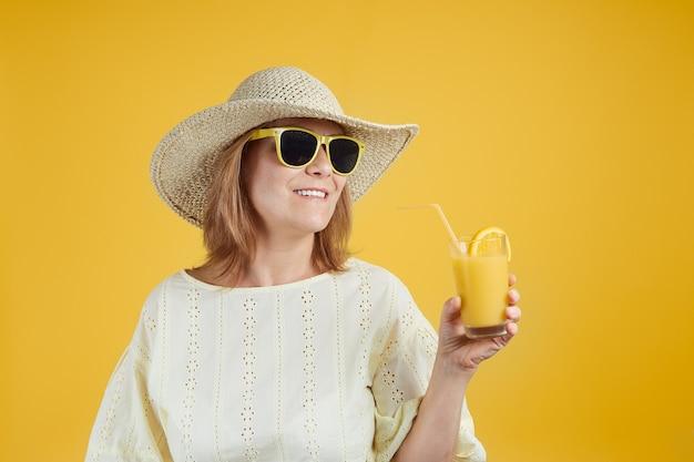 Reife frau mit strohhut in sonnenbrille hält ein glas orangensaft auf hellgelbem b...