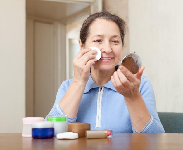 Reife frau reinigt das make-up