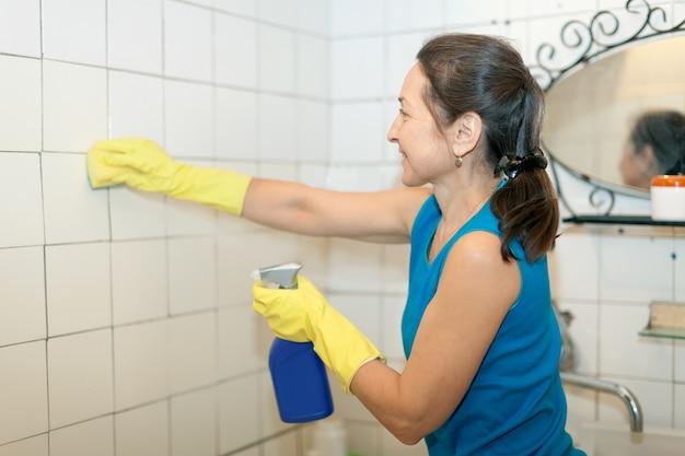 Reife frau reinigt fliesen im badezimmer