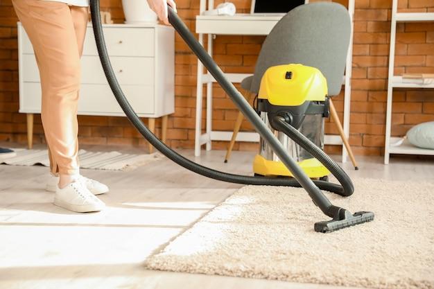 Reife frau saugt teppich zu hause