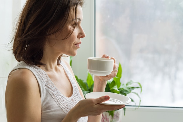 Reife frau trinkt morgenkaffee und schaut aus dem fenster